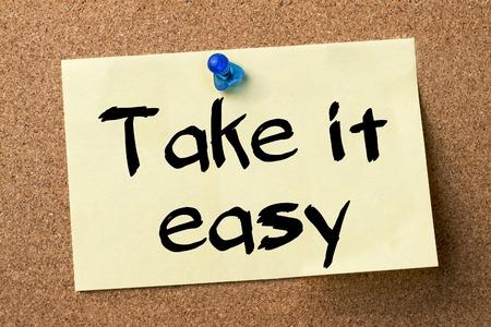 take it easy: Take it easy - adhesive label pinned on bulletin board - horizontal image