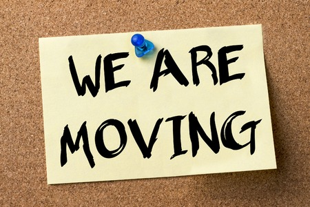 WE ARE MOVING - adhesive label pinned on bulletin board - horizontal image Stock Photo