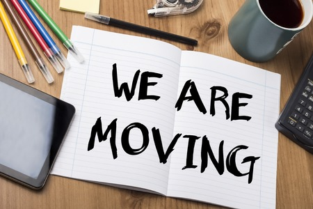 WE ARE MOVING - Note Pad With Text On Wooden Table - with office  tools Stock Photo