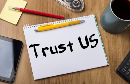 note pad: Trust US - Note Pad With Text On Wooden Table - with office  tools Stock Photo