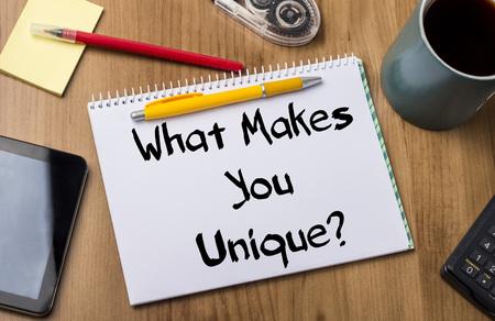 Wat maakt je uniek? - Notitieblok met tekst op houten tafel - met office tools Stockfoto