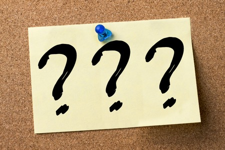 Three question marks - adhesive label pinned on bulletin board - horizontal image