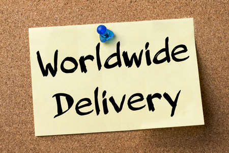 bulletin: Worldwide Delivery - adhesive label pinned on bulletin board - horizontal image Stock Photo