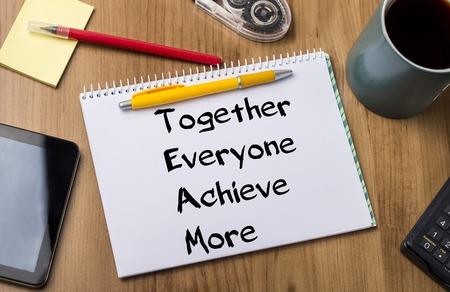 strong message: Together Everyone Achieve More TEAM - Note Pad With Text On Wooden Table - with office  tools Stock Photo