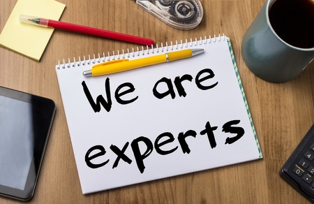 We are experts - Note Pad With Text On Wooden Table - with office  tools