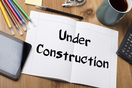 vision repair: Under Construction - Note Pad With Text On Wooden Table - with office  tools Stock Photo