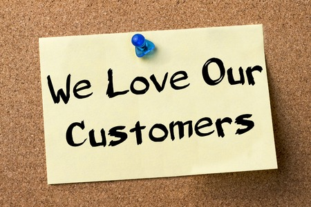 We Love Our Customers - adhesive label pinned on bulletin board - horizontal image