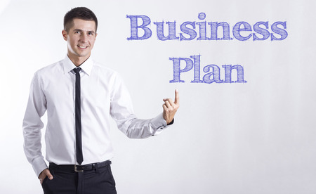 Business Plan - Young smiling businessman pointing on text - horizontal images