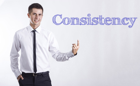 Consistency - Young smiling businessman pointing on text - horizontal images
