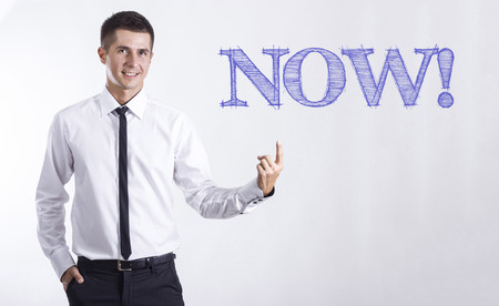 NOW! - Young smiling businessman pointing on text - horizontal images Stok Fotoğraf