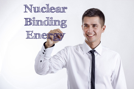 Nuclear Binding Energy - Young smiling businessman writing on transparent surface - horizontal images Stok Fotoğraf