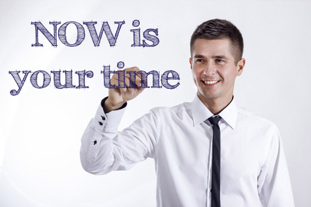 NOW is your time - Young smiling businessman writing on transparent surface - horizontal images