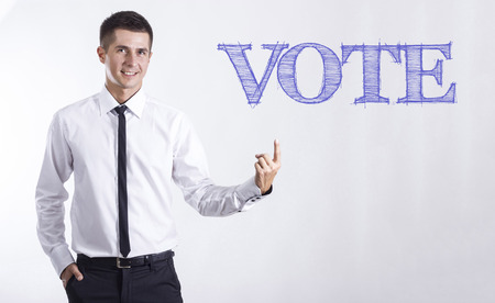 VOTE - Young smiling businessman pointing on text - horizontal images
