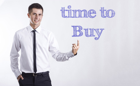Time to Buy - Young smiling businessman pointing on text - horizontal images