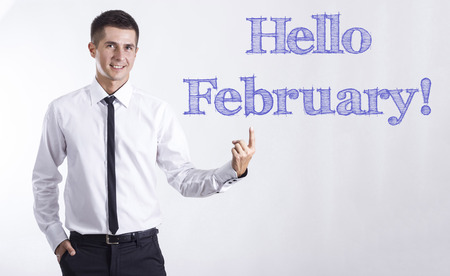Hello February! - Young smiling businessman pointing on text - horizontal images