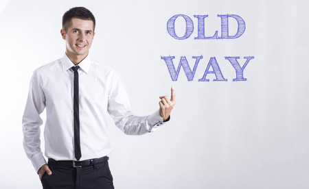 OLD WAY - Young smiling businessman pointing on text - horizontal images
