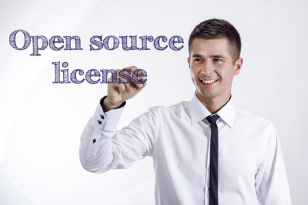 Open source license - Young smiling businessman writing on transparent surface - horizontal images Stok Fotoğraf