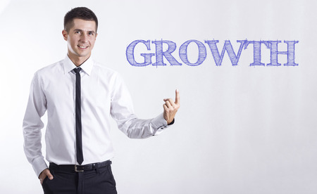 GROWTH - Young smiling businessman pointing on text - horizontal images