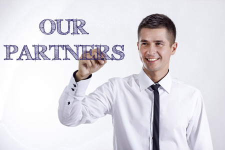 OUR PARTNERS - Young smiling businessman writing on transparent surface - horizontal images Stok Fotoğraf