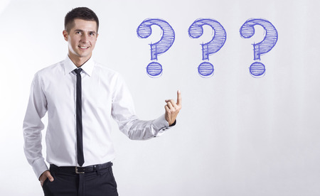 Three question mark - Young smiling businessman pointing on text - horizontal images