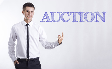 AUCTION - Young smiling businessman pointing on text - horizontal images