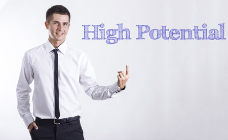 High Potential - Young smiling businessman pointing on text - horizontal images