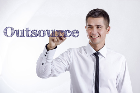 Outsource - Young smiling businessman writing on transparent surface - horizontal images