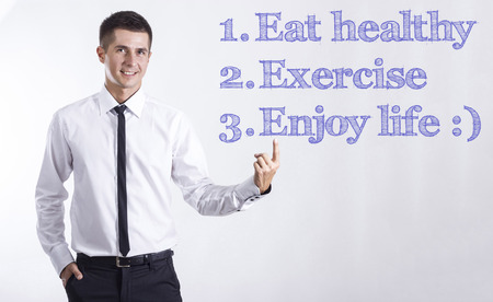 1.  Eat healthy 2. Exercise 3. Enjoy life :) - Young smiling businessman pointing on text - horizontal images