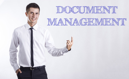DOCUMENT MANAGEMENT - Young smiling businessman pointing on text - horizontal images