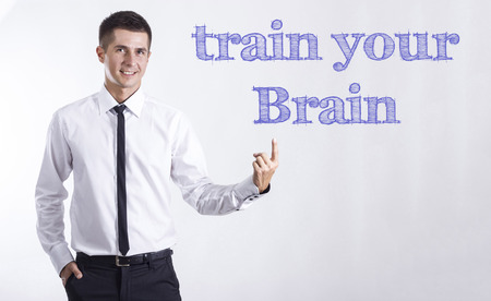Train your Brain - Young smiling businessman pointing on text - horizontal images