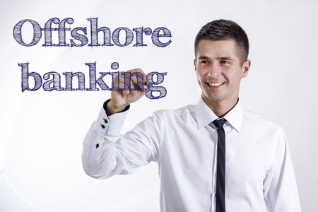 earned: Offshore banking - Young smiling businessman writing on transparent surface - horizontal images Stock Photo