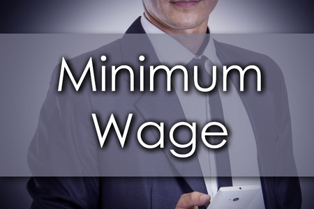 Minimum Wage - Young businessman with text - business concept - horizontal image Banco de Imagens