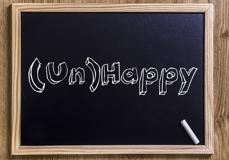 (Un)Happy - New chalkboard with outlined text - on wood Stock Photo