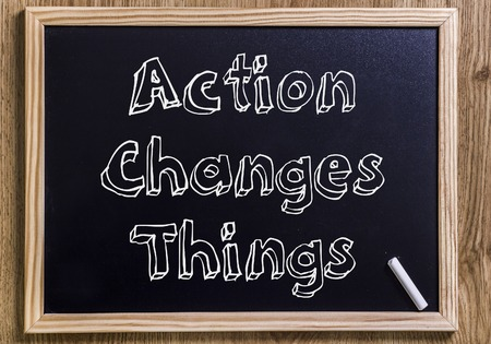 Action Changes Things - New chalkboard with outlined text - on wood Stock Photo