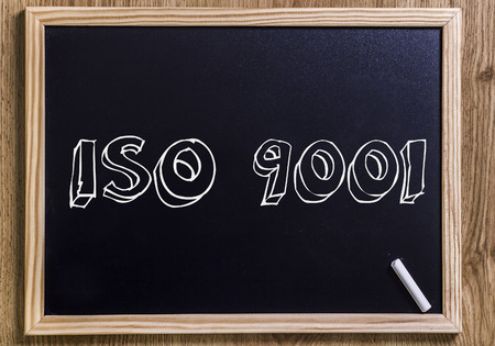 ISO 9001 - New chalkboard with outlined text - on wood Stock Photo