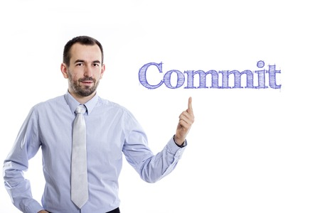 Commit - Young businessman with small beard pointing up in blue shirt - horizontal image Stok Fotoğraf