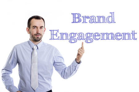 Brand Engagement - Young businessman with small beard pointing up in blue shirt - horizontal image 写真素材