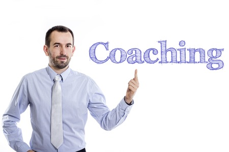 Coaching - Young businessman with small beard pointing up in blue shirt - horizontal image