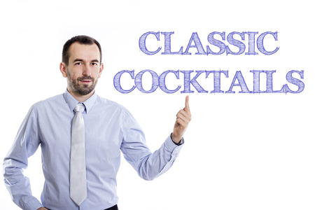 CLASSIC COCKTAILS - Young businessman with small beard pointing up in blue shirt - horizontal image