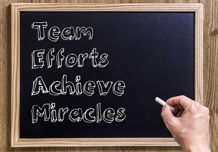 Team Efforts Achieve Miracles - New chalkboard with 3D outlined text - on wood Stock Photo - 72944443