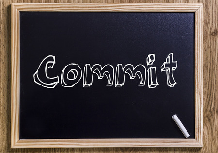 Commit - New chalkboard with outlined text - on wood Stock Photo