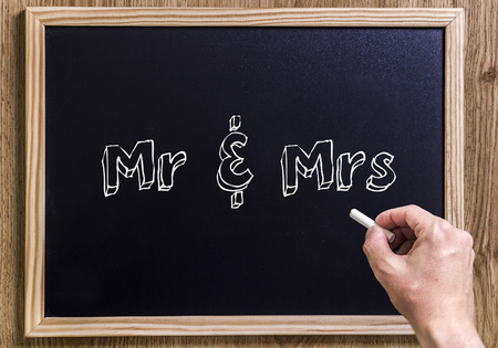 Mr & Mrs - New chalkboard with 3D outlined text - on wood - with hand Stock Photo