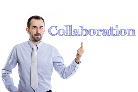 Collaboration - Young businessman with small beard pointing up in blue shirt - horizontal image