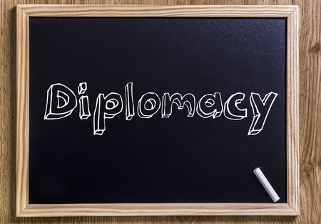 Diplomacy - New chalkboard with outlined text - on wood Stock Photo