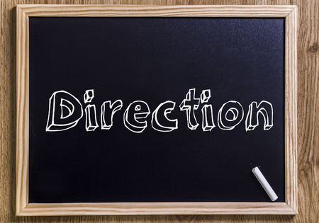 Direction - New chalkboard with outlined text - on wood Stock Photo