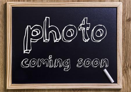 foto komt binnenkort - Nieuw krijtbord met omlijnde tekst - op hout Stockfoto