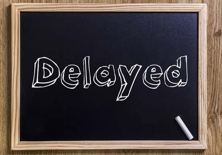 Delayed - New chalkboard with outlined text - on wood Stock Photo