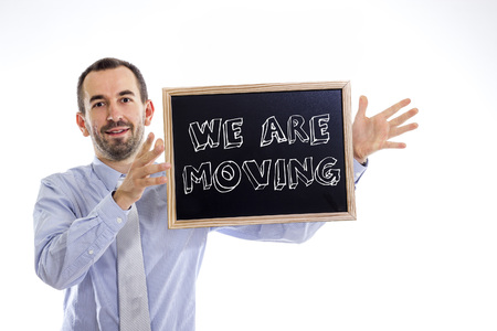 We are moving - Young businessman with blackboard - isolated on white - horizontal image