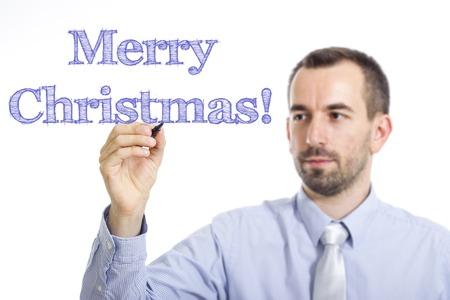 Joyeux Noël! Jeune homme d'affaires écrit un texte en bleu sur une surface transparente - image horizontale Banque d'images - 73089868