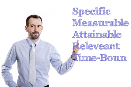 specific: Specific Measurable Attainable Releveant Time-Bound SMART - Young businessman with small beard pointing up in blue shirt - horizontal image